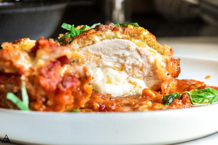 Sliced stuffed chicken parmesan in a plate