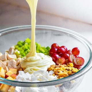 Pouring the dressing into the ingredients for chicken salad with grapes