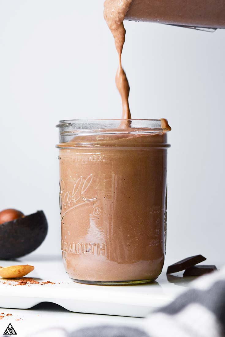 Pouring low carb peanut butter smoothie in a glass