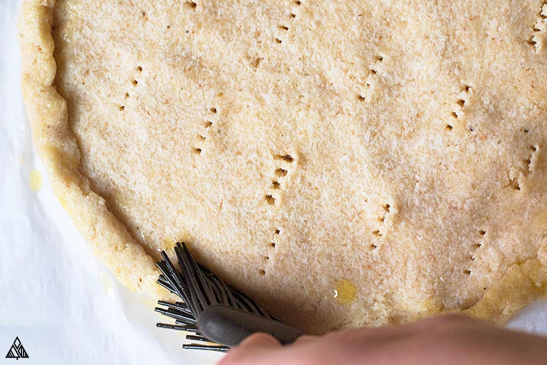 Adding oil into the low carb pizza crust using a brush