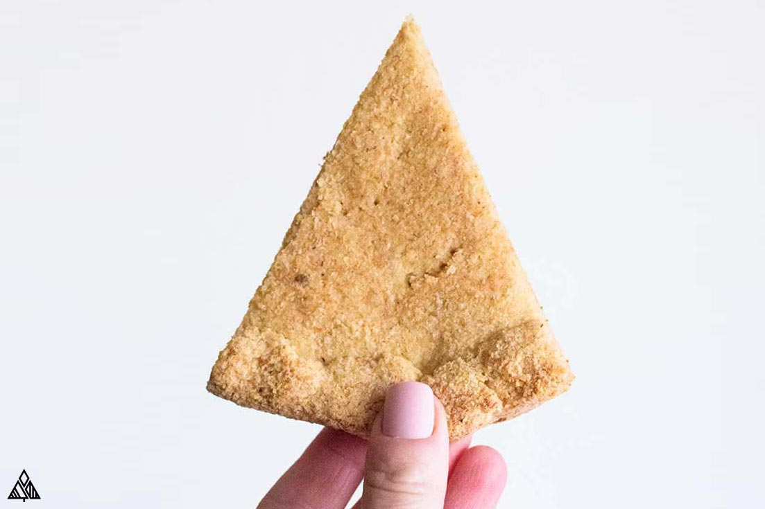 Holding a slice of low carb pizza crust