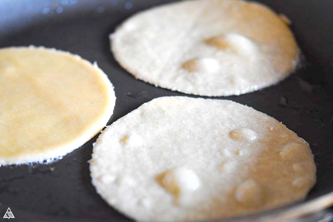 Cooking 3 almond flour tortillas in a pan