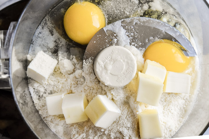 Eggs and slices of butter in a food processor