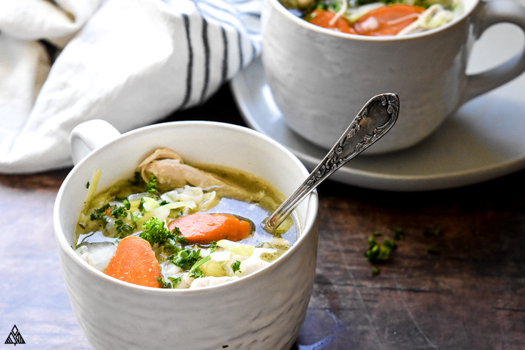 Side view of low carb chicken soup in a cup