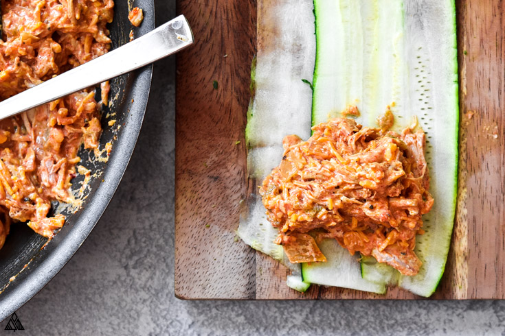 Adding meat into the thin slices of zucchini