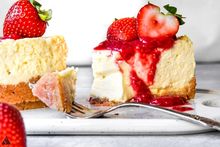 A slice of cheesecake with low carb graham cracker crust topped with strawberries